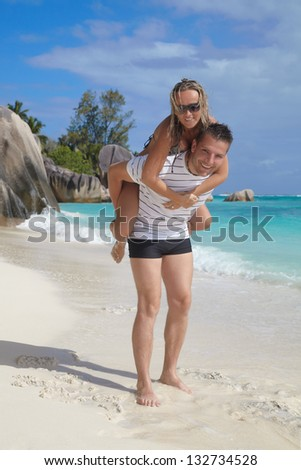Two young adults having fun on the white sandy beach at exotic island