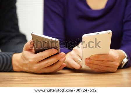 two young adults sharing music and files over mobile smart phones - stock photo