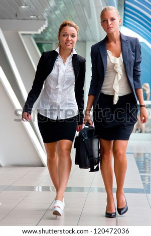 Two young and beautiful business woman in a business center