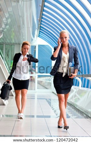 Two young and beautiful business woman in a business center - stock photo