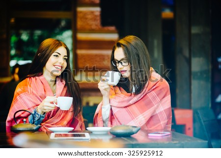 Two young and beautiful girls gossiping on the terrace with a cup of coffee