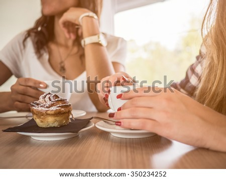 Two young and beautiful women meet at the bar for a cappuccino and to chat - stock photo