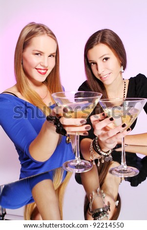 Two young and cheerful girlfriends with colorful cocktails - stock photo