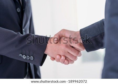 Two young and successful businessmen rejoice in the success of their language matters. Handsome young men shake their hands. Confident men smiling in formal suit - stock photo