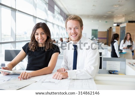 Two young architects working in an office, smiling to camera - stock photo