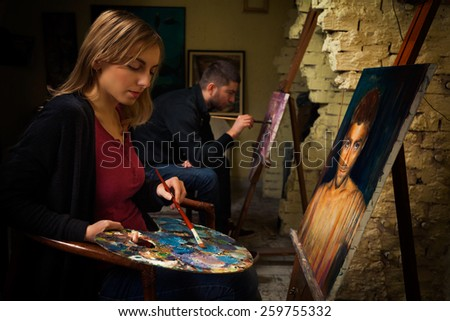 Two young art students working on oil paintings in art studio. - stock photo