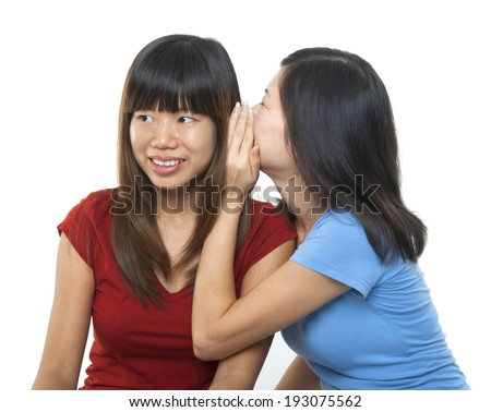 Two young Asian girls sharing secrets, isolated on white background.