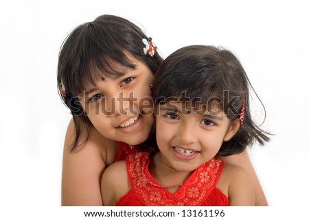 Two young Asian girls showing sisterly affection and smiles - stock photo