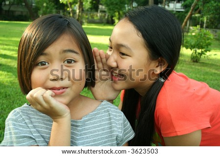 Two young asian kids whispering. - stock photo