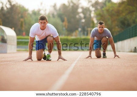 Two young athletes in starting position ready to run a race - stock photo