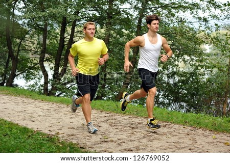 Two young athletes jogging / running in the park - stock photo