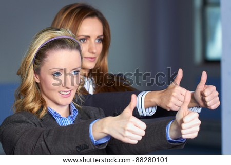 Two Young attractive females in business suits show thumb up gesture - stock photo