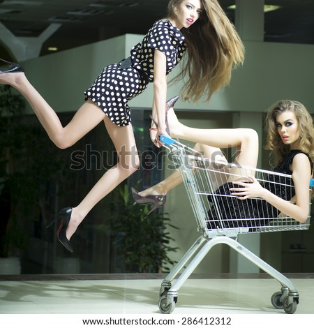 Two young attractive funny fashionable girls in dresses with shopping trolley indoor on store backdrop, sqare picture - stock photo