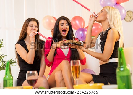 Two young attractive girls, elegantly dressed, prepared surprise their friends, giving her a birthday cake, playing in the party whistles.