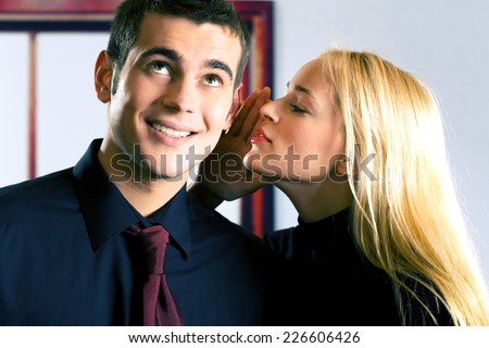 Two young attractive happy smiling business people or couple telling a secret, indoors
