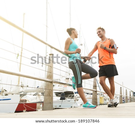 Two young attractive joggers leaning against railing having a water break - stock photo