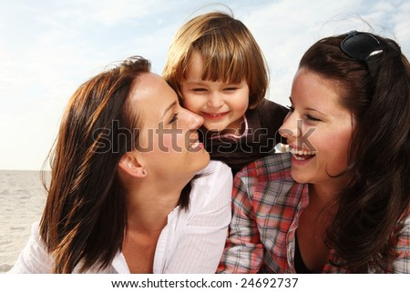 Two young attractive woman and small child laughing on the beach.