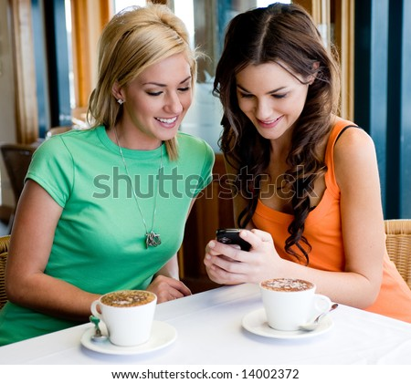 Two young attractive women drinking coffee at a restaurant and looking at phone - stock photo