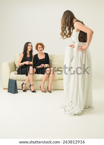 two young attractive women sitting on sofa and laughing while other woman models a dress - stock photo