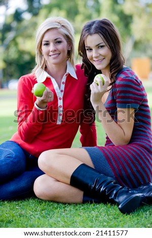 Two young attractive women sitting outside on the lawn with apples