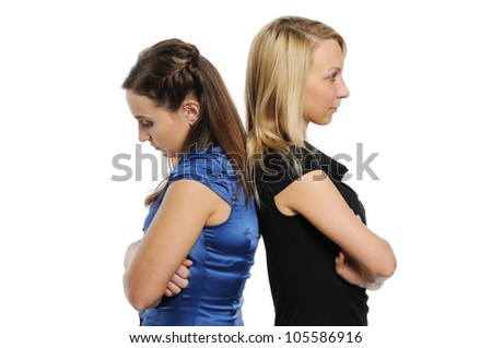 Two young attractive women standing back to back. Isolated on white. - stock photo