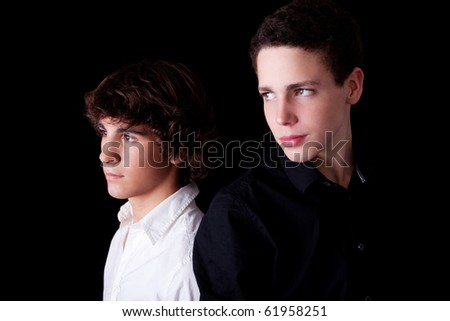 two young back to back, isolated on black, studio shot - stock photo
