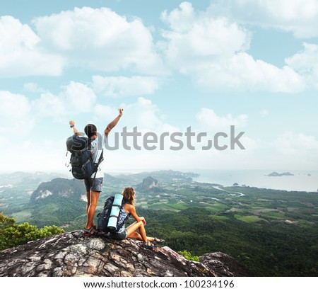 Two young backpackers enjoying a valley view from top of a mountain - stock photo