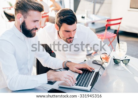 Two young bearded caucasian modern business man sitting in a bar, using laptop, looking downward, tapping on keyboard  - business, work, technology concept - focus on black hair man - stock photo
