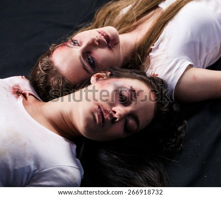 Two young beaten women with cuts and bruises lie down on the floor on black background - stock photo