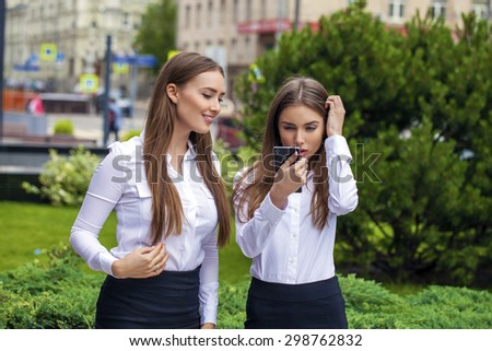 Two Young beautiful business women in white shirt on summer street - stock photo