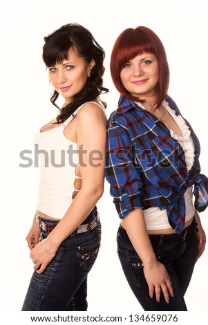 Two young beautiful casual girls wearing jeans smiling isolated on white