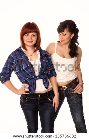 Two young beautiful casual girls wearing jeans smiling isolated on white - stock photo