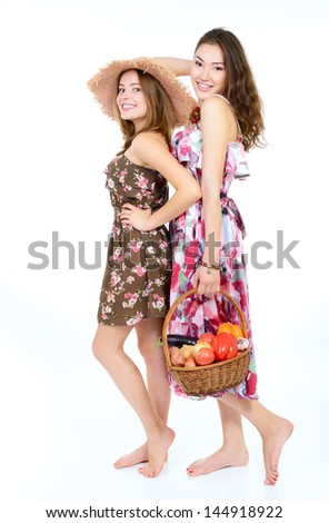 two young beautiful cheerful friends women holding baskets with vegetables and fruits ready for summer picnic - stock photo
