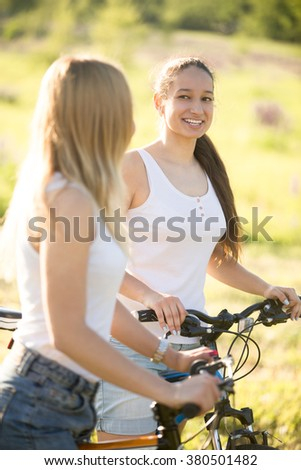 Two young beautiful cheerful women girlfriends wearing jeans shorts on bicycles in park on sunny summer day, having good time, talking to each other - stock photo
