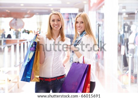 Two young beautiful girls are engaged in shopping in a store