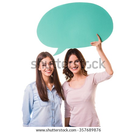 Two young beautiful girls holding green bubble for text, isolated on a white background - stock photo
