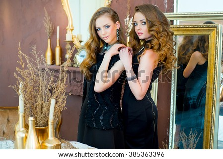 Two young beautiful girls in black evening dress with elegant jewelry posing in a gold interior zone
