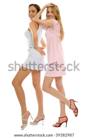 Two young beautiful girls in stylish dresses and stilettos, on white background