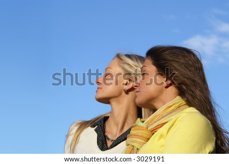 Two young beautiful girls over sky background
