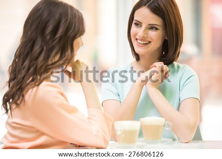 Two young beautiful girls sitting in urban cafe with coffee and sharing secrets. - stock photo