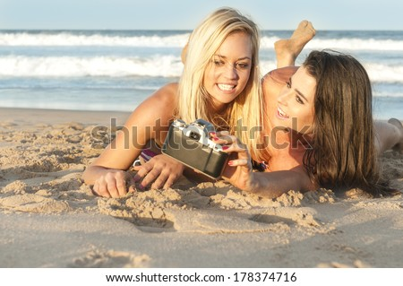 two young beautiful girls taking selfie with film camera - stock photo