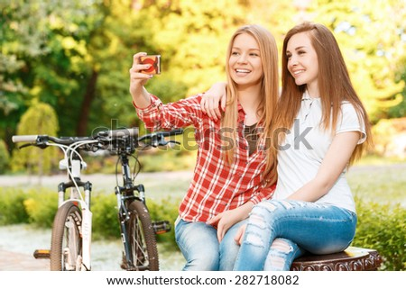 Two young beautiful happy girls sitting on a bench in a green park smiling and making selfie on a colorful smartphone, their sport bikes standing near, selective focus - stock photo