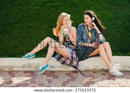 two young beautiful happy stylish hipster girls, cocktail, smoozy drink, denim, smiling, happy, fashion, cool accessories, amazed, vintage style, having fun, park, sitting, grass, sneakers, copyspace - stock photo