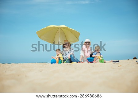 Two young beautiful mother with the boys on the beach - stock photo