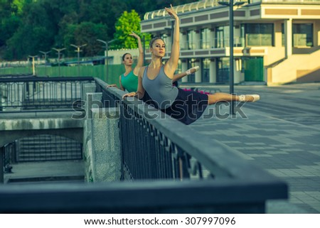 Two young beautiful twin sister dancing ballet in the city with ballet costume. urban sync dance. Developed from RAW. retouched with special care and attention. - stock photo