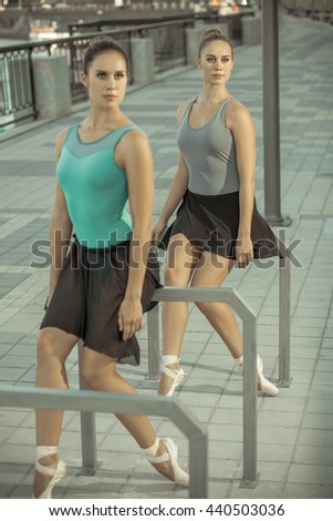 Two young beautiful twin sister dancing ballet in the city with ballet costume. urban sync dance. industrial street dancing. with special effect. synced posing. pointe ballet shoes and dress.