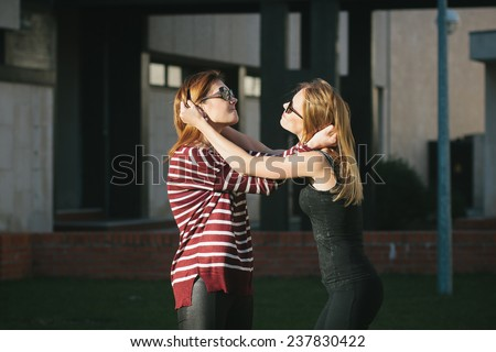Two young beautiful woman fighting craving for each other's hair - stock photo