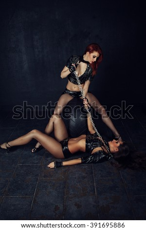 Two Young beautiful woman playing in slave, with chains on a black background - stock photo