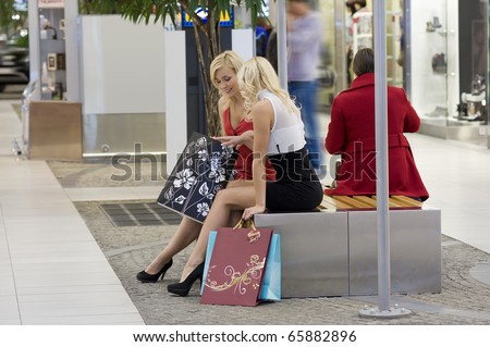two young beautiful woman sitting on a bench inside a commercial center go for shopping with bags - stock photo