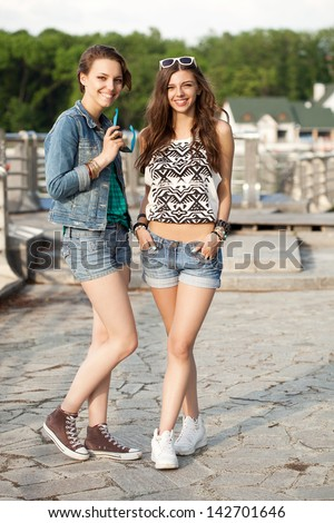 Two young beautiful woman walking near the water. Outdoors, lifestyle - stock photo